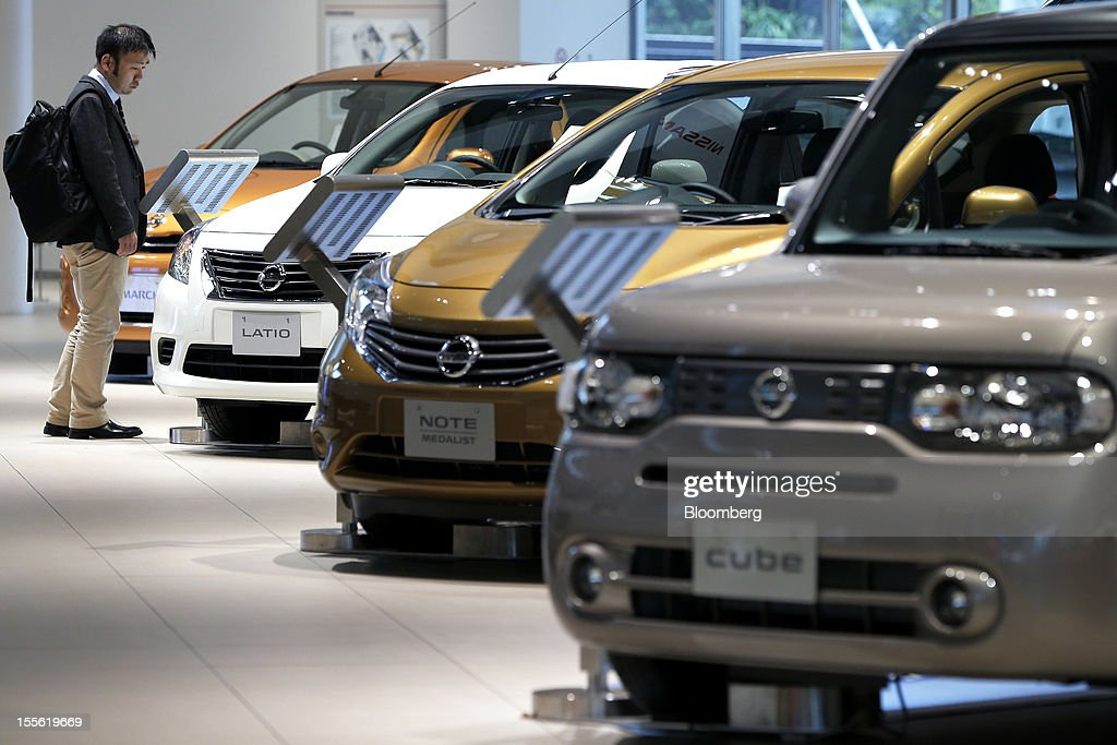 A visitor looks at Nissan Motor Co. vehicles displayed at the company's headquarters in Yokohama City, Kanagawa Prefecture, Japan, on Tuesday, Nov. 6, 2012. Nissan, the top Japanese seller of vehicles in China, cut its full-year net income forecast 20 percent after consumer backlash stemming from a territorial dispute sent sales lower in its largest market. Photographer: Kiyoshi Ota/Bloomberg via Getty Images