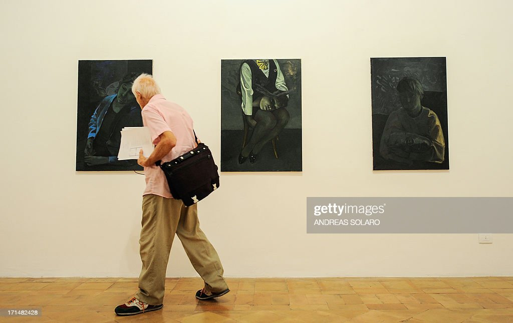 A visitor looks at paintings by Romanian artist Victor Man on June 25, 2013 during an exhibition at the Villa Medici, the headquarters of the French Academy in Rome.