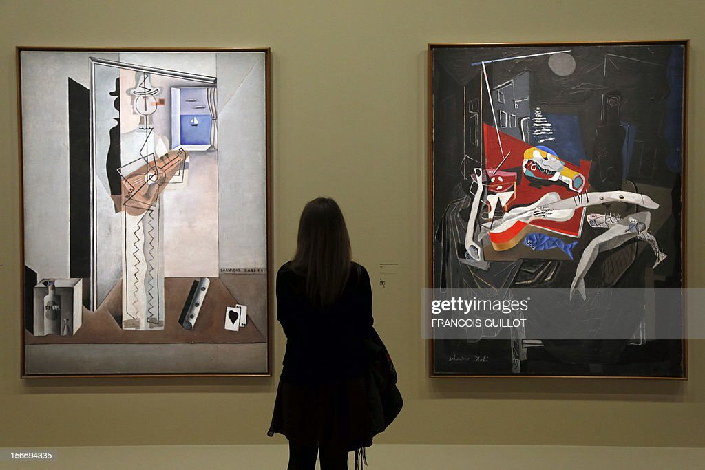 A visitor looks at paintings by Spanish surrealist artist Salvador Dali's during an exhibition devoted to his work at the Centre Pompidou contopary art center (aka Beaubourg) on November 19, 2012 in Paris. More than 30 years after the first retrospective in 1979, the event gathers more than 200 art pieces and runs until March 13, 2013. (LtoR) 'Pierrot Playing the Guitar' and 'Still Life by Moonlight'.