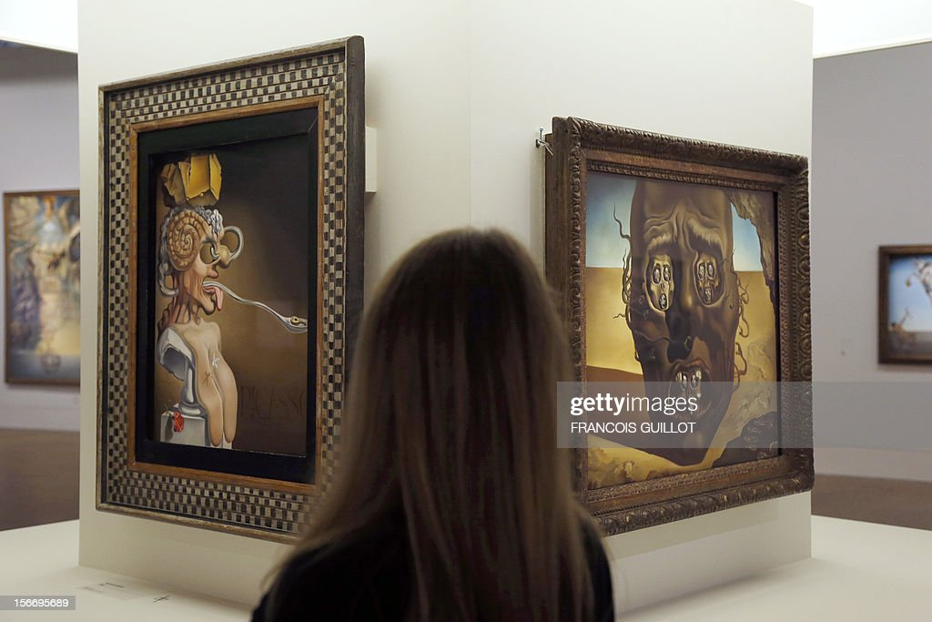 A visitor looks at paintings by Spanish surrealist artist Salvador Dali during an exhibition devoted to his work at the Centre Pompidou contemporary art center (aka Beaubourg) on November 19, 2012 in Paris. More than 30 years after the first retrospective in 1979, the event gathers more than 200 art pieces and runs until March 13, 2013. (L) 'Portraits of Picasso', (R) 'Le visage de la guerre' (The face of war'). AFP PHOTO FRANCOIS GUILLOT