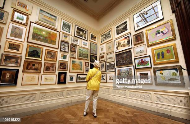 A visitor looks at paintings hanging in The Weston Room at The Royal Academy Summer Exhibition on June 9 2010 in London England The RA Summer...