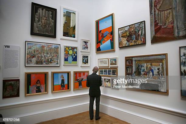 A visitor looks at paintings in the Summer Exhibition at The Royal Academy on June 3 2015 in London England The RA Summer exhibition is the world's...