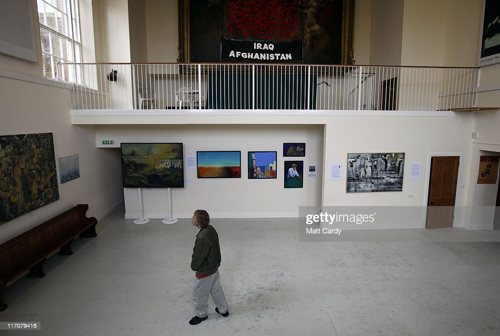 A visitor looks at paintings inside Exeter Castle on June 21, 2011 in Exeter, England. The paintings are among artworks produced by former and current servicemen and women currently being exhibited at Exeter Castle. The free exhibition, Entrance to War Art, aims to foster understanding between Post Traumatic Stress Disorder (PTSD) sufferers and the wider community and runs until Sunday.