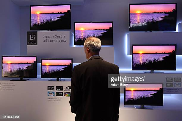 A visitor looks at Panasonic ETW5 energy efficient Smart TV flatscreen televisions at the Internationale Funkausstellung 2012 consumer electronics...
