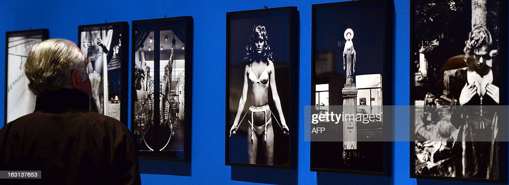 A visitor looks at photos by German-Australian photographer Helmut Newton during a press preview of the 'White women / Sleepless nights / Big nudes' exhibition at the Palazzo delle Esposizioni on March 5, 2013 in Rome. The exhibition will run from March 6 to July 21, 2013.