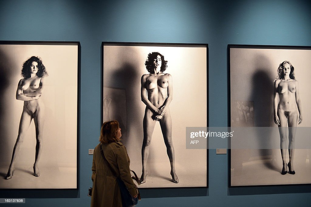 A visitor looks at photos by German-Australian photographer Helmut Newton during a press preview of the 'White women / Sleepless nights / Big nudes' exhibition at the Palazzo delle Esposizioni on March 5, 2013 in Rome. The exhibition will run from March 6 to July 21, 2013. AFP PHOTO / GABRIEL BOUYS RESTRICTED TO EDITORIAL USE, MANDATORY CREDIT OF THE ARTIST, TO ILLUSTRATE THE EVENT AS SPECIFIED IN THE CAPTION