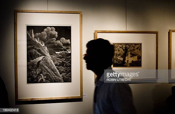 A visitor looks at piece by world famous Dutch graphic artist MC Escher at Soestdijk Palace in Baarn on August 16 2012 The exhibition ' MC Escher...