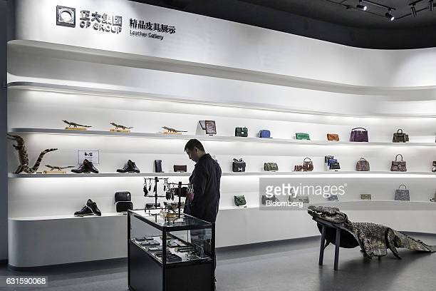 A visitor looks at products made of crocodile leather on display in the visitor center at the Chai Tai Saimese Crocodile Breeding Base at a Charoen...