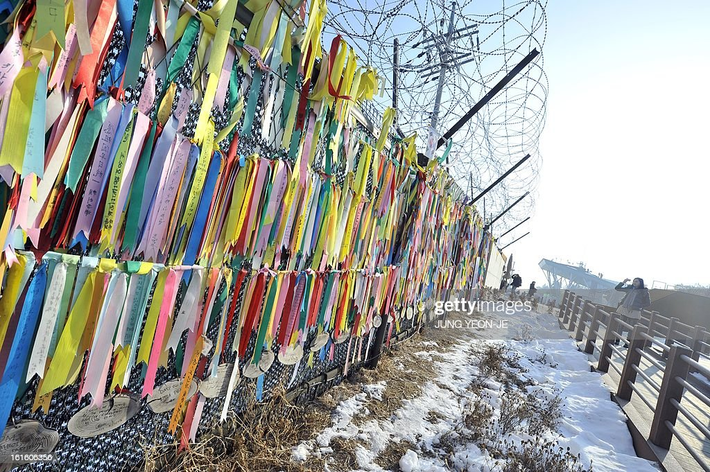 A visitor looks at 'reunification ribbons' displayed on a military iron fence at Imjingak peace park in Paju near the demilitarized zone dividing the two Koreas on February 13, 2013. South Korea said on February 13 it would accelerate the development of longer-range ballistic missiles that could cover the whole of North Korea in response to a third nuclear test by Pyongyang.