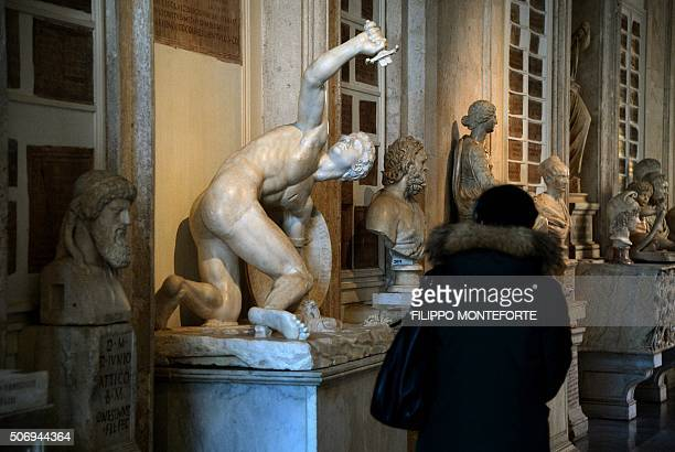 A visitor looks at Roman marble statues on display at Rome's Capitoline Museum on Capitol Hill on January 26 2016 Italy's desire to court visiting...