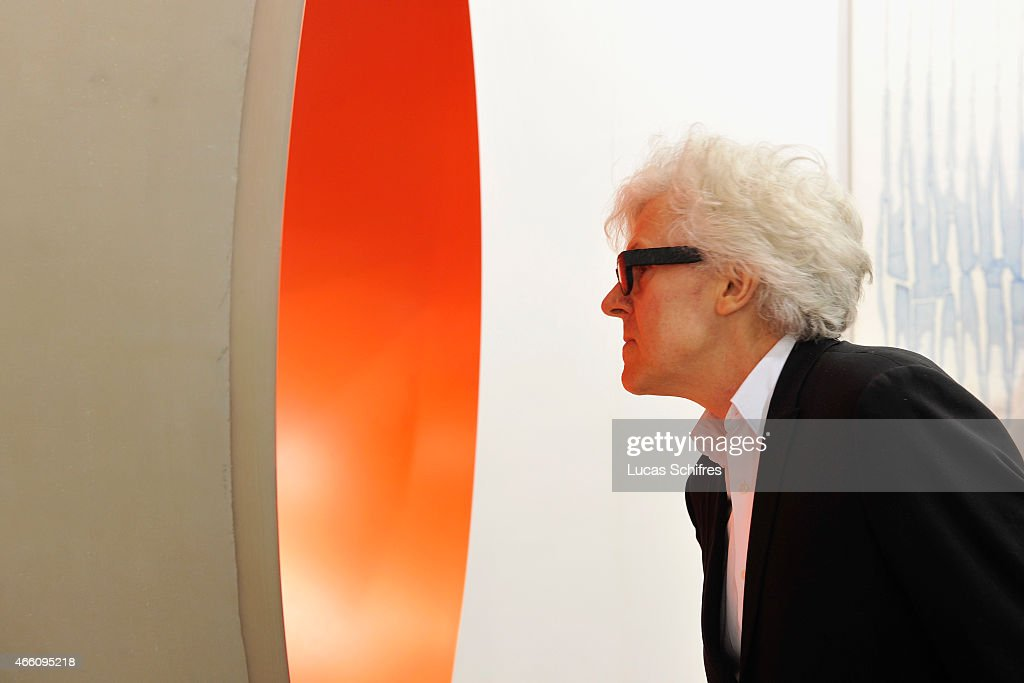 A visitor looks at sculpture 'Monochrome (Neon Orange)' by Anish Kapoor on the preview day of Art Basel art fair on March 13, 2015 in Hong Kong, Hong Kong.