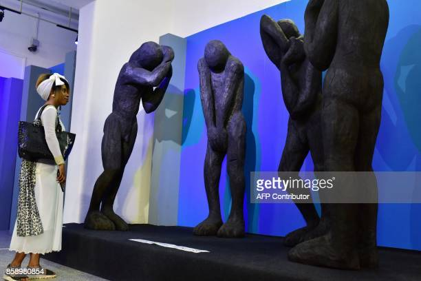 A visitor looks at statues as she visits the Civilisation Museum of Abidjan on September 29 2017 during the first exhibition called 'Renaissance'...