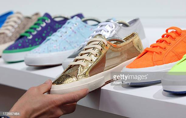 A visitor looks at Superga shoes from Italy on display during the Bread and Butter trade show at the former Tempelhof airport during MercedesBenz...