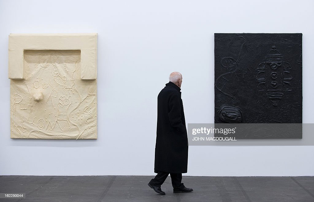 A visitor looks at the 1991 work 'Untitled' (from the series Black Rubber Paintings) by German artist Martin Kippenberger (1953-1997), on display at the exhibition 'Martin Kippenberger Sehr Gut / Very Good' at Berlin's Hamburger Bahnhof museum for contemporary art on February 21, 2013. The exhibition, a retrospective of the artist's prolific and varied output opens from February 23 to August 18, 2013.
