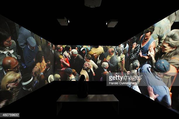 A visitor looks at the artwork 'Face in the Crowd' by Alex Prager in the Unlimited section of Art Basel on June 17 2014 in Basel Switzerland Art...