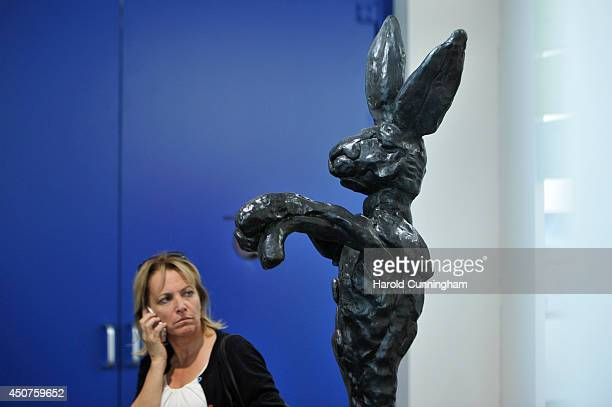 A visitor looks at the artwork 'Large Boxing Hare on Anvil' by Barry Flanagan in the gallery section of Art Basel on June 17 2014 in Basel...