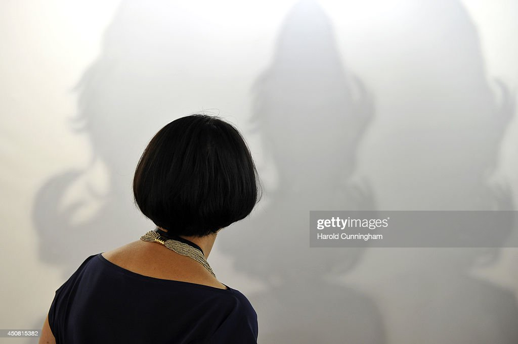A visitor looks at the artwork 'Shadow' by Jiro Takamatsu in the gallery section of Art Basel on June 18, 2014 in Basel, Switzerland. Art Basel one of the most prestigious art fair in the world, which runs until the 22nd of June 2014 will showcase the work of more than 4,000 artists selected by 300 leading galleries.