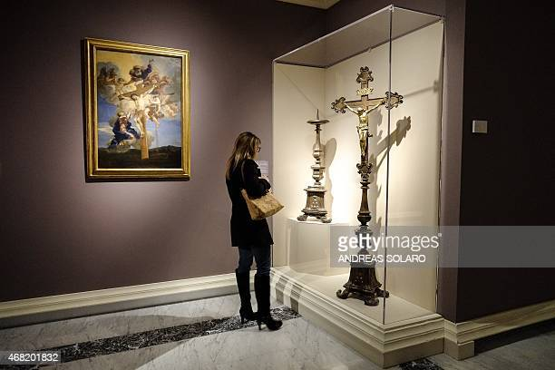 A visitor looks at the candlestick and crucifix for one of the altars in the Vatican Basilica and the painting ' Sanguis Christi ' of Italian painter...