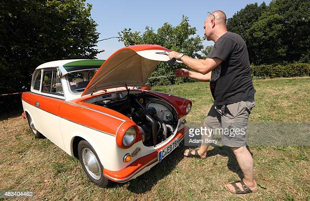 A visitor looks at the engine of his 1963 Trabant P60 automobile at a Trabant enthusiasts' weekend on August 8 2015 near Nossen Germany The Trabant...