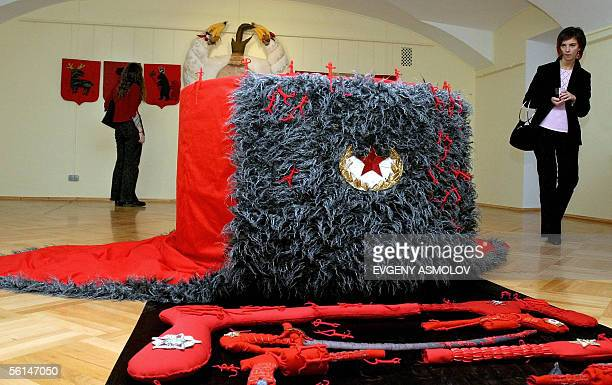A visitor looks at the huge military stile Russian warm cap and rag weapon at the exhibition of the artist Dmitry Tsvetkov 'Russian empire cap with...
