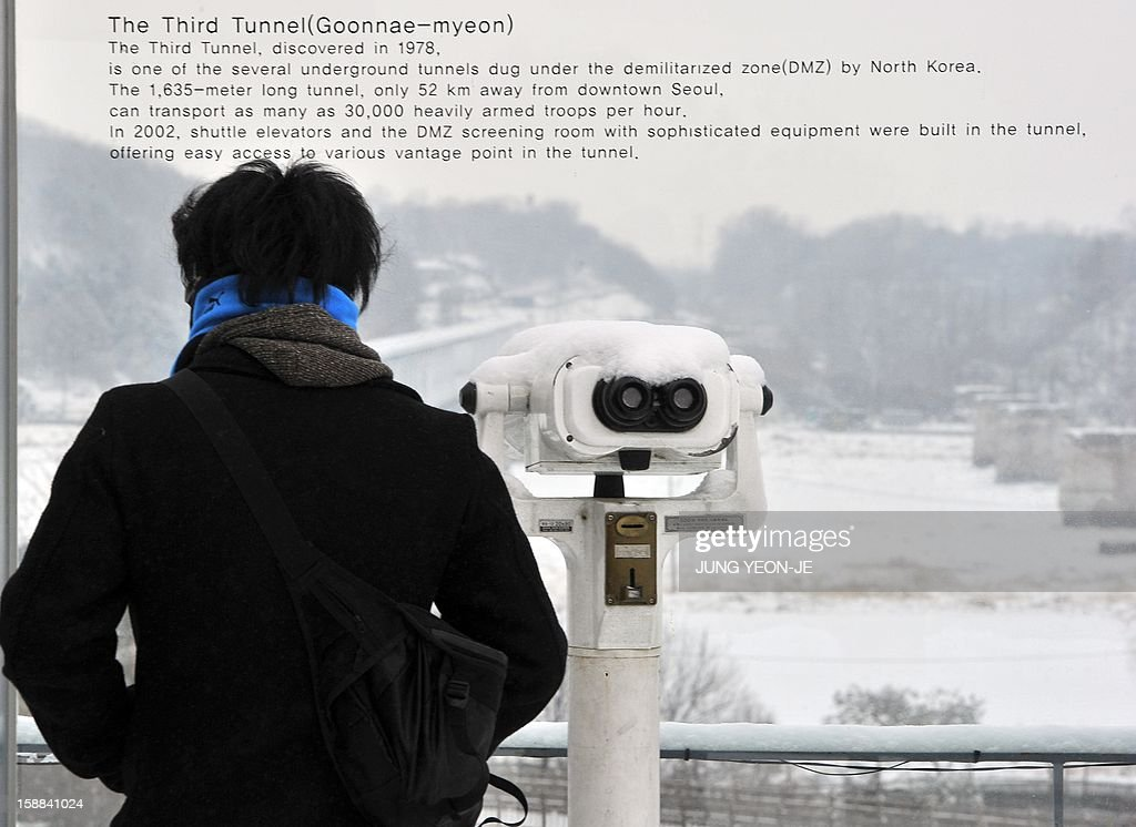 A visitor looks at the North side from an observation tower of Imjingak peace park in Paju near the Demilitarized Zone (DMZ) dividing the two Koreas on January 1, 2013. North Korean leader Kim Jong-Un called on January 1, 2013 for an easing of tensions with the South and flagged a 'radical turnabout' in the national economy in a rare voiced message broadcast on state television.