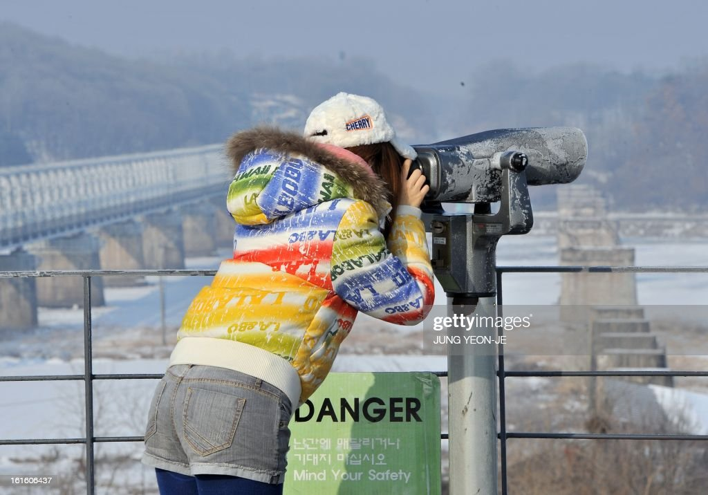 A visitor looks at the North side through binoculars at Imjingak peace park in Paju near the demilitarized zone dividing the two Koreas on February 13, 2013. South Korea said on February 13 it would accelerate the development of longer-range ballistic missiles that could cover the whole of North Korea in response to a third nuclear test by Pyongyang. AFP PHOTO / JUNG YEON-JE