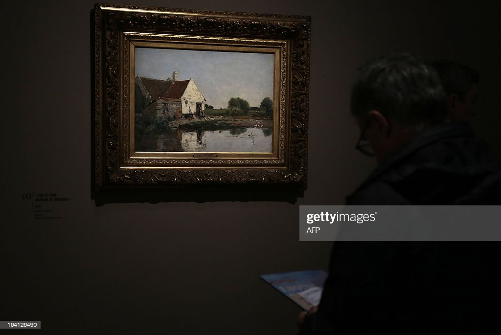 A visitor looks at the painting, ''coin de ferme (environs de Dunkerque)' on March 20, 2013 at the Jacquemart-Andre museum during the inaugural visit to the French painter Eugene Boudin's (1824 - 1898) exhibition running from March 22 to July 22, 2013. AFP PHOTO/JACQUES DEMARTHON