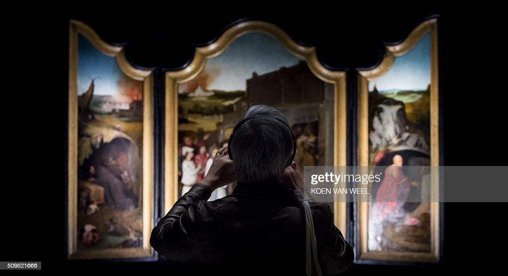 A visitor looks at the painting Job-drieluik (Job-triptych) painted by Dutch Renaissance artist Jheronimus Bosch (or Hieronymus, or Jeroen Bosch) during a press preview of the exhibition 'Hieronymus Bosch - Visions of a Genius' at the Noordbrabants Museum in Den Bosch on February 11, 2016. The exhibition will run from February 13 till May 8, 2016. / AFP / ANP / Koen van Weel