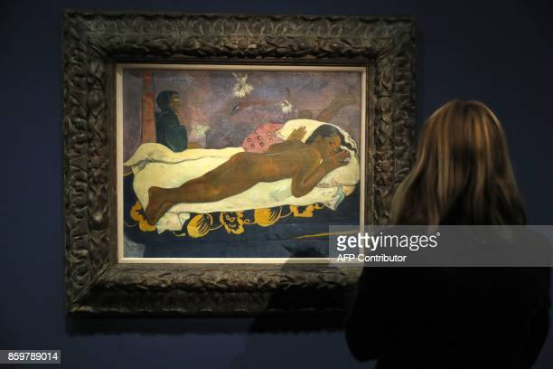 A visitor looks at the painting 'Manao Tupapau ' by French painter Paul Gauguin during the exhibition entitled 'Gauguin the alchimist' at the Grand...