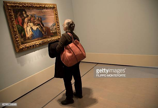 A visitor looks at the painting of 1548 'Lamentation over the dead Christ' by Paolo Veronese at the Scuderie del Quirinale in Rome on December 15...