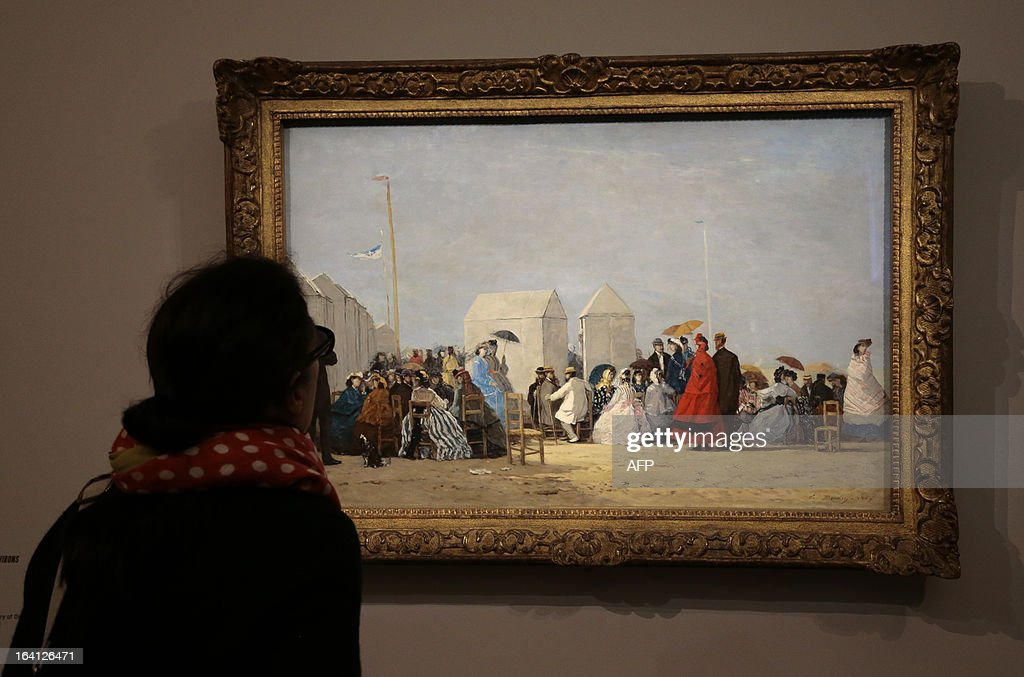 A visitor looks at the painting, ' plage aux environs de Trouville' on March 20, 2013 at the Jacquemart-Andre museum during the inaugural visit to the French painter Eugene Boudin's (1824 - 1898) exhibition running from March 22 to July 22, 2013.