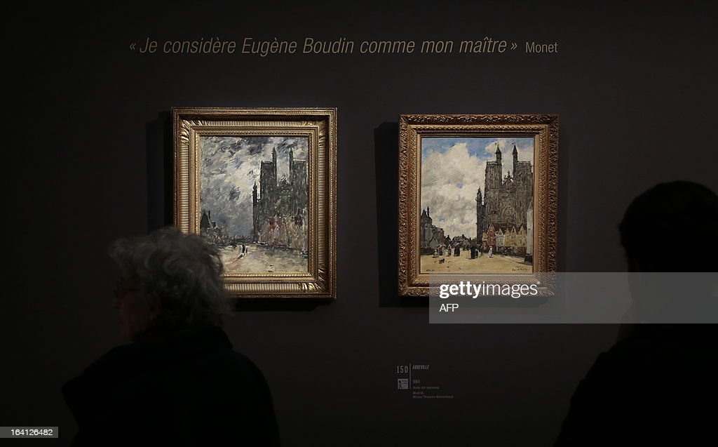 A visitor looks at the paintings, 'Abbeville de nuit' (L) and 'Abbeville' on March 20, 2013 at the Jacquemart-Andre museum during the inaugural visit to the French painter Eugene Boudin's (1824 - 1898) exhibition running from March 22 to July 22, 2013.