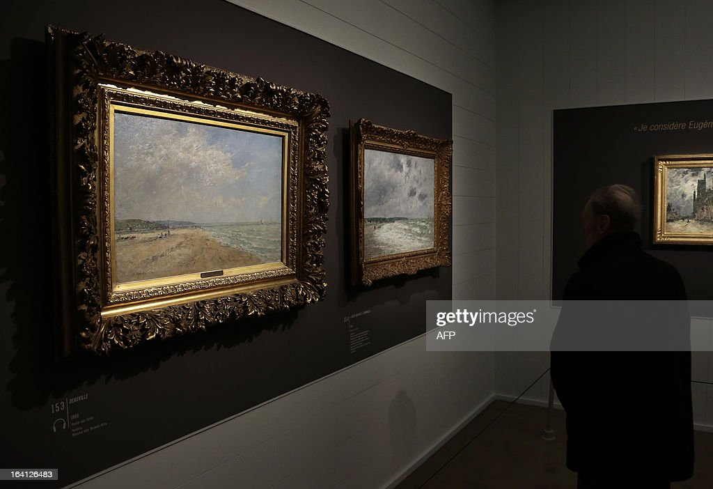 A visitor looks at the paintings, 'Deauville' (L) and ' maree montante a Deauville' on March 20, 2013 at the Jacquemart-Andre museum during the inaugural visit to the French painter Eugene Boudin's (1824 - 1898) exhibition running from March 22 to July 22, 2013.