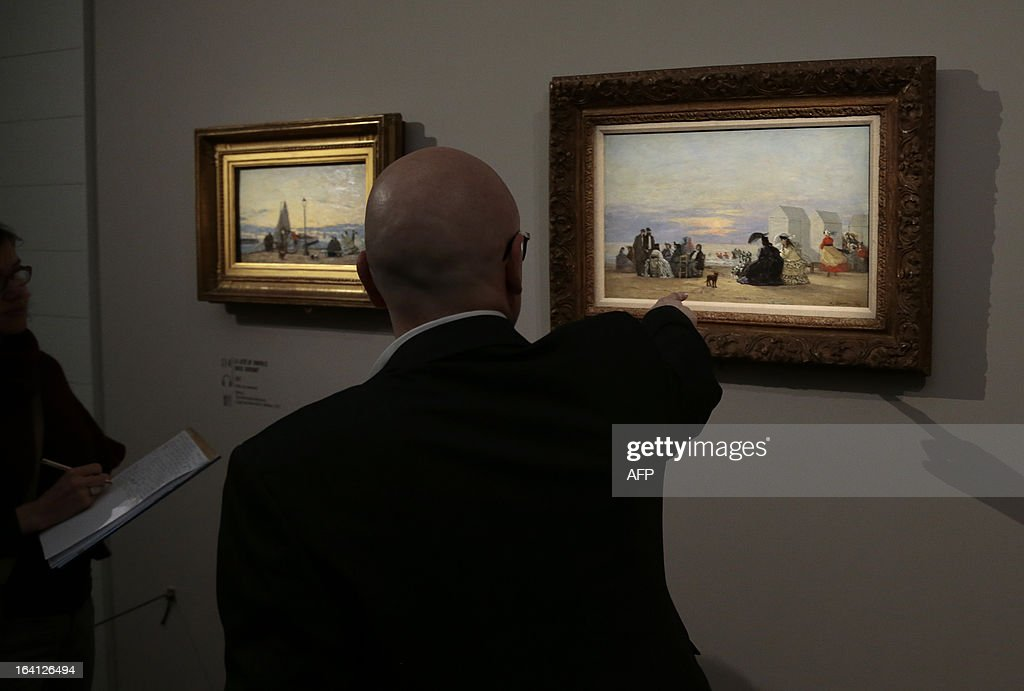 A visitor looks at the paintings, 'la jetee de Trouville, soleil couchant' (L) and 'plage, au soir', on March 20, 2013 at the Jacquemart-Andre museum during the inaugural visit to the French painter Eugene Boudin's (1824 - 1898) exhibition running from March 22 to July 22, 2013.