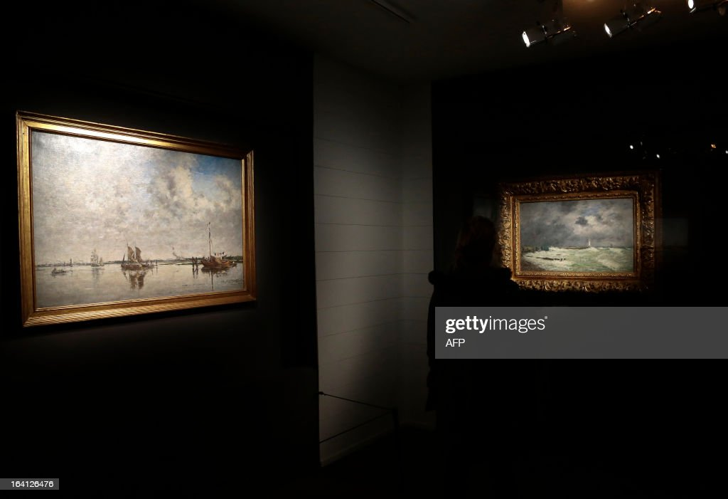 A visitor looks at the paintings, 'la Meuse, a Rotterdam' (L) and 'coup de vent devant Frascati ' on March 20, 2013 at the Jacquemart-Andre museum during the inaugural visit to the French painter Eugene Boudin's (1824 - 1898) exhibition running from March 22 to July 22, 2013.
