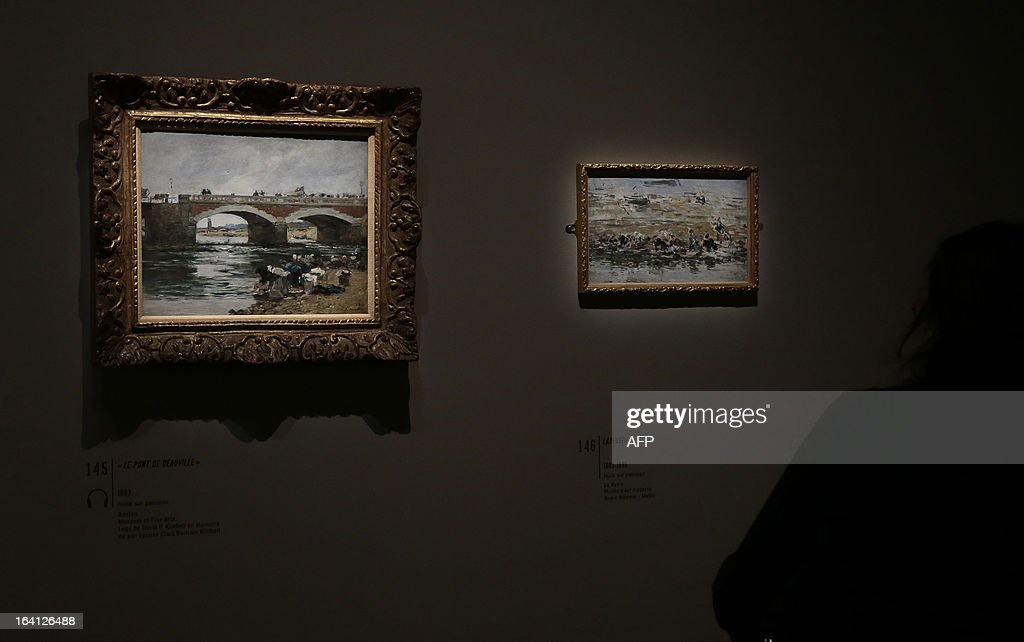 A visitor looks at the paintings, 'le pont de Deauville' (L) and 'laveuses' on March 20, 2013 at the Jacquemart-Andre museum during the inaugural visit to the French painter Eugene Boudin's (1824 - 1898) exhibition running from March 22 to July 22, 2013.