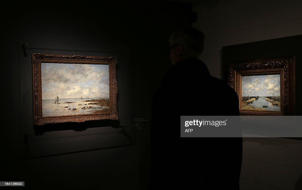 A visitor looks at the paintings, 'maree basse a Saint-Vaast-la-Hougue' (L) and 'entree du port de Trouville a la maree basse' (D) on March 20, 2013 at the Jacquemart-Andre museum during the inaugural visit to the French painter Eugene Boudin's (1824 - 1898) exhibition running from March 22 to July 22, 2013.
