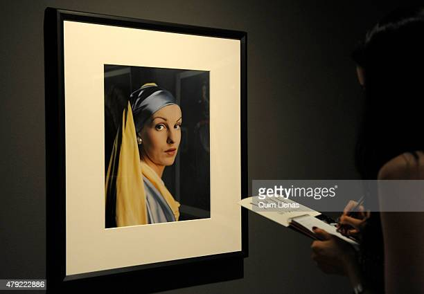 A visitor looks at the photograph titled 'Girl with a Pearl Earring' by Erwin Blumenfeld during the opening for the press of 'Vogue like a painting'...
