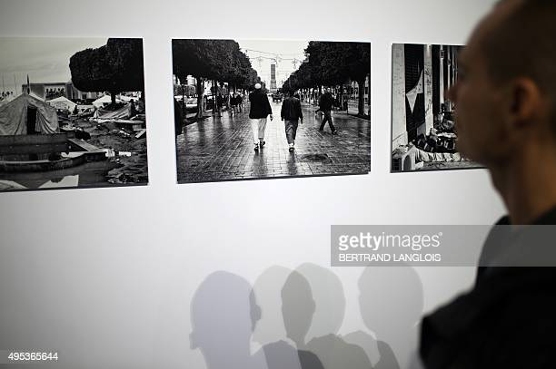 A visitor looks at the photographs 'Fragments of a revolution' by Tunisian artist Wassim Ghozlani as part of the exhibition 'J'aime les panoramas' at...