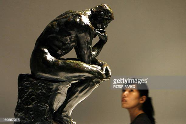 A visitor looks at the sculpture 'The Thinker' by French artist Auguste Rodin at Beijing's World Art Museum 30 May 2006 The show features 60 late...