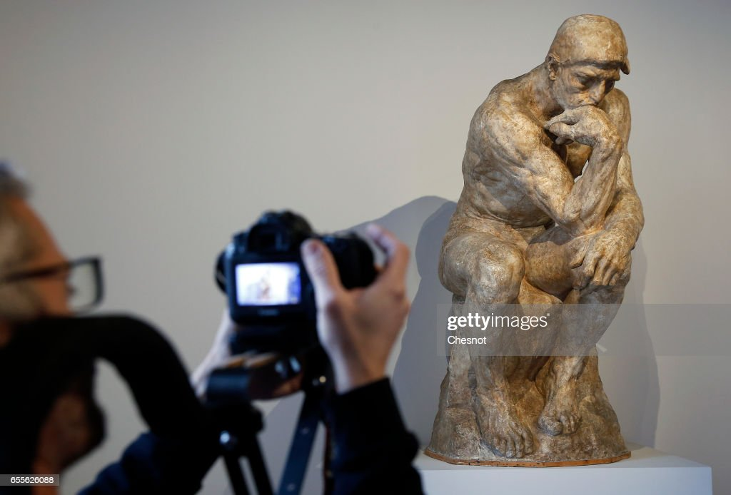 A visitor looks at the sculpture ' The Thinker, 1903, enlargement according to the statuette of 1881-1882ÊÈ by French sculptor Auguste Rodin (1840-1917) during the press preview 'Rodin the centennial exhibition' at the Grand-Palais on March 20, 2017 in Paris, France. To mark the centenary of his death, the Rodin museum and the Grand-Palais are joining forces to celebrate Auguste Rodin (1840-1917). This exhibition takes part from March 22 to July 31, 2017.