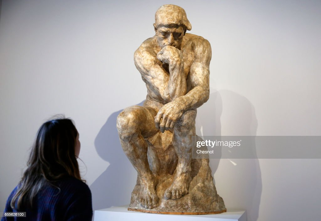 A visitor looks at the sculpture 'The Thinker, 1903, enlargement according to the statuette of 1881-1882' by French sculptor Auguste Rodin (1840-1917) during the press preview 'Rodin the centennial exhibition' at the Grand-Palais on March 20, 2017 in Paris, France. To mark the centenary of his death, the Rodin museum and the Grand-Palais are joining forces to celebrate Auguste Rodin (1840-1917). This exhibition takes part from March 22 to July 31, 2017.
