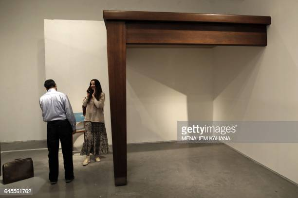 A visitor looks at the 'Table Leg' installation by artist Robert Therrien in the Bedroom section of the No Place Like Home exhibition in the Israel...