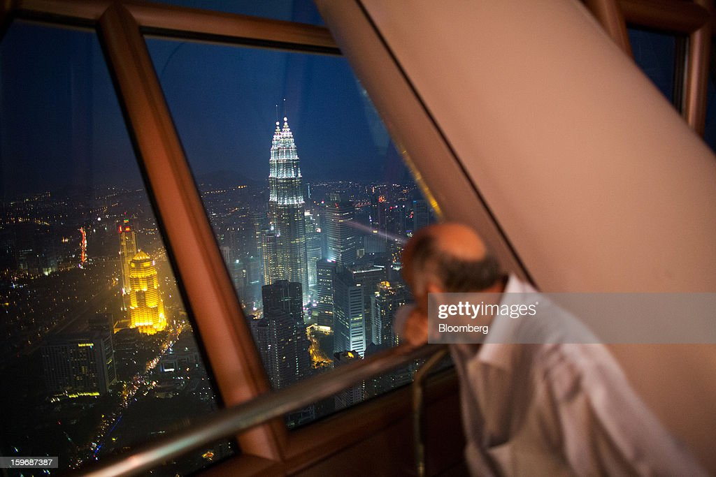 A visitor looks at the view from the observation deck at Kuala Lumpur Tower as the Petronas Towers stand illuminated at night in Kuala Lumpur, Malaysia, on Wednesday, Jan. 16, 2013. While many developed countries have faltered, Malaysia's gross domestic product growth has exceeded 5 percent for five quarters with domestic demand countering a slowdown in exports. Photographer: Lam Yik Fei/Bloomberg via Getty Images
