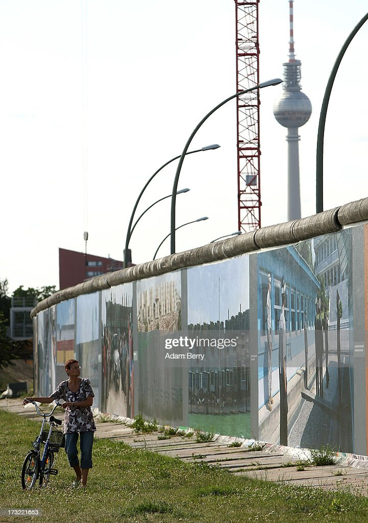 A visitor looks at the 'Wall on Wall' exhibition at the East Side Gallery section of the former Berlin Wall on July 10, 2013 in Berlin, Germany. A series of photos shot since 2006 by photographer Kai Wiedenhoefer hanging on the Western, river Spree side of the Wall features large pictures of separation barriers in Baghdad, Korea, Cyprus, Mexico, Morocco, Israel, Belfast, and in the former East Germany itself. The opposite side of the stretch of the original Wall is known as East Side Gallery, a memorial to peace and freedom covered in murals questioning the legacy of the original Wall, and the subject of several demonstrations earlier in March this year when a section of it were threatened with removal to make way for a construction site for luxury apartment buildings, discussion of which is still ongoing with a decision expected to be reached in early August.