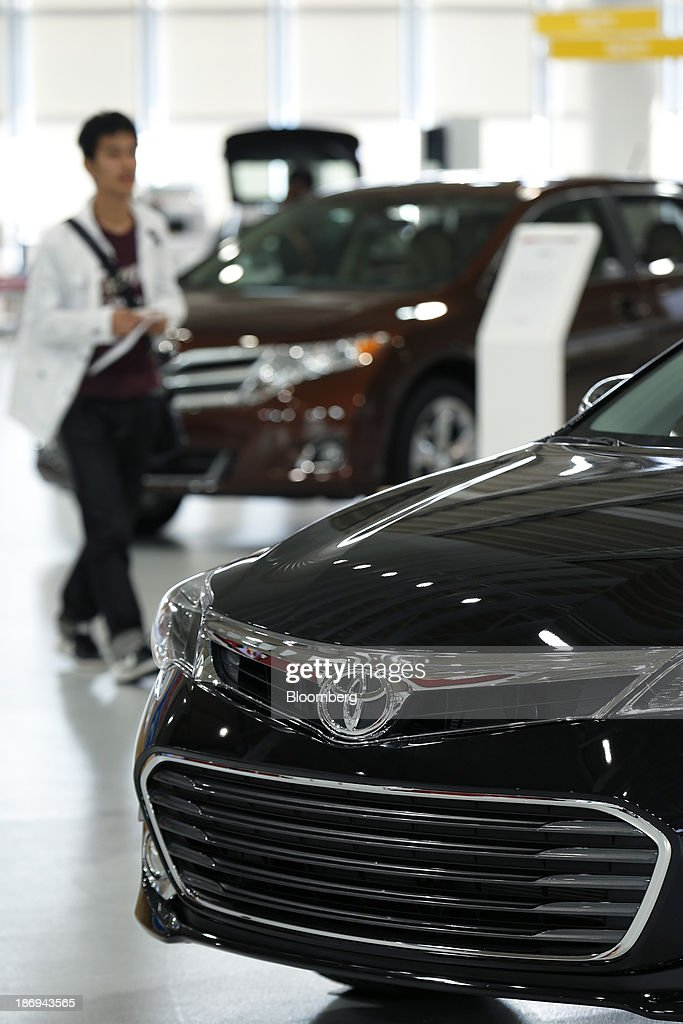 A visitor looks at Toyota Motor Corp. Avalon, front, and Venza vehicles on display at the company's showroom in Tokyo, Japan, on Tuesday, Nov. 5, 2013. Toyota, the world's largest automaker, will probably deliver record semiannual profit when it reports earnings tomorrow, as the weaker yen bolsters the value of Japanese cars sold overseas. Photographer: Kiyoshi Ota/Bloomberg via Getty Images