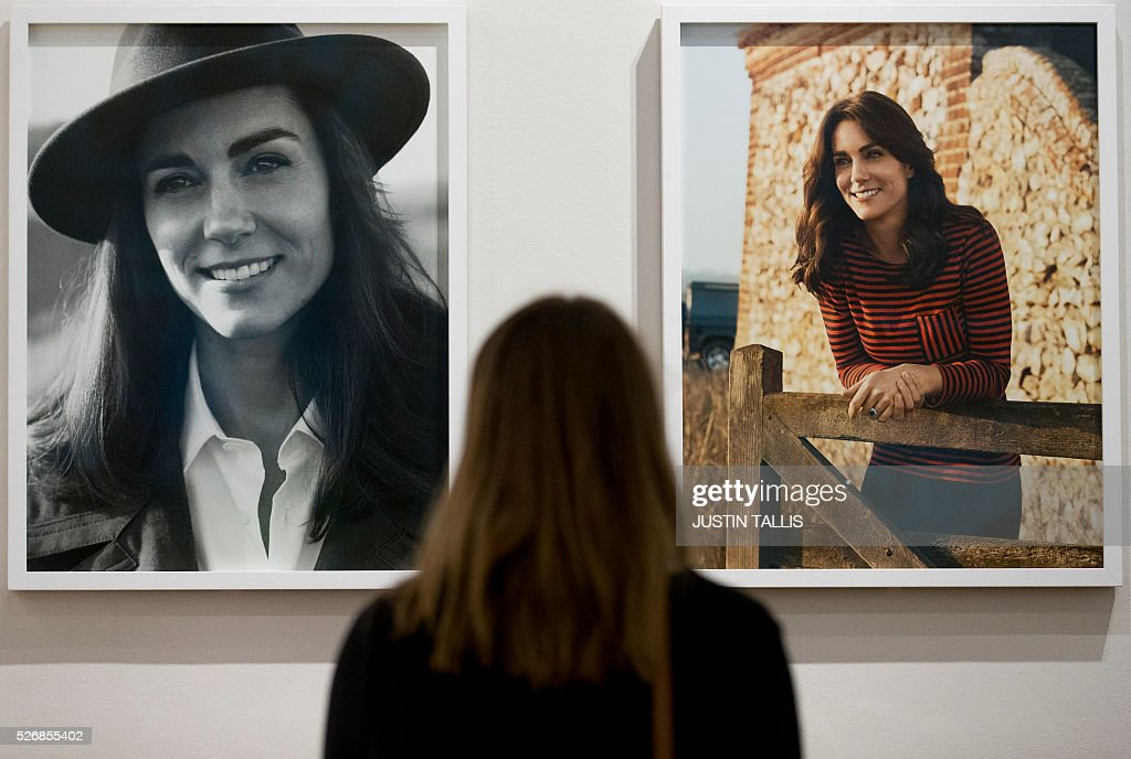 A visitor looks at two new portraits of Catherine, Duchess of Cambridge, taken in the Norfolk Countryside by British photographer Josh Olins, at the Vogue 100: A Century of Style exhibition at the National Portrait Gallery in London on May 1, 2016. / AFP / JUSTIN
