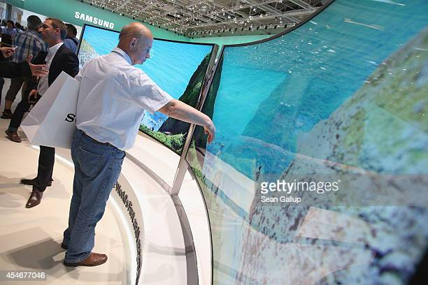 A visitor looks at Ultra HD curved displays at the Samsung stand at the 2014 IFA home electronics and appliances trade fair on September 5 2014 in...
