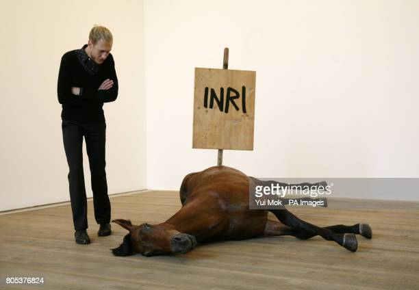 A visitor looks at 'Untitled' by artist Maurizio Cattelan during a press preview of the exhibition Pop Life Art in a Material World at Tate Modern in...