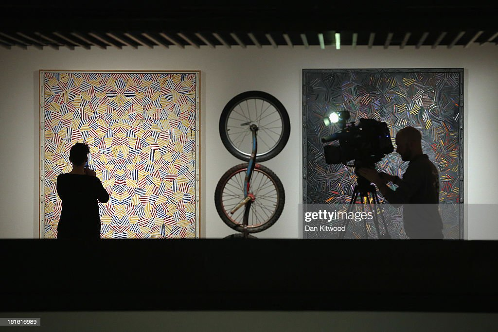 A visitor looks at works by Jasper Johns (L) as a cameraman films a piece by Robert Rauschenberg during a press preview of 'The Bride and the Bachelors' exhibition at the Barbican Art Gallery on February 13, 2013 in London, England. The piece makes up a selection of works by artists and choreographers including Marcel Duchamp, Merce Cunningham, John Cage, Robert Rauschenberg and Jasper Johns, and runs at the Barbican Art Gallery until June 9, 2013.